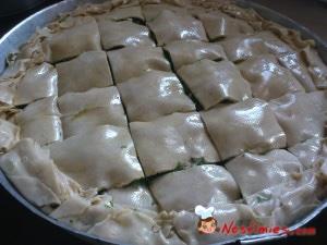 Με ένα μυτερό μαχαίρι χαράζουμε την πίτα σε τετράγωνα κομμάτια και την βάζουμε σε φούρνο που τον έχουμε προθερμάνει στους 180 βαθμούς.