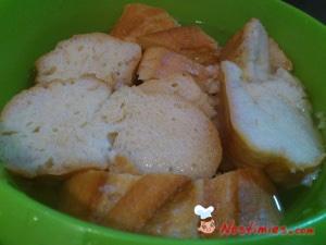 Κόβουμε το ψωμί σε φέτες και το βάζουμε σε μια λεκανίτσα με νερό μέχρι να μαλακώσει και το στραγγίζουμε πολύ καλά.