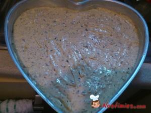 Βουτυρώνουμε καλά μία φόρμα (κατά προτίμηση σε σχήμα καρδιάς) στην βάση και στα πλαϊνά με φυτικό βούτυρο. Ρίχνουμε το μίγμα και ψήνουμε το κέϊκ σε προθερμασμένο φούρνο στους 180 βαθμούς για 50 λεπτά περίπου. Δεν ανοίγουμε τον φούρνο στα πρώτα 30 λεπτά για να φουσκώσει καλά. Καταλαβαίνουμε ότι έχει ψηθεί βυθίζοντας την μύτη ενός μαχαιριού που θα βγει καθαρή και βλέποντας ότι έχει ξεχωρίσε το κέϊκ στις άκρες από την φόρμα.